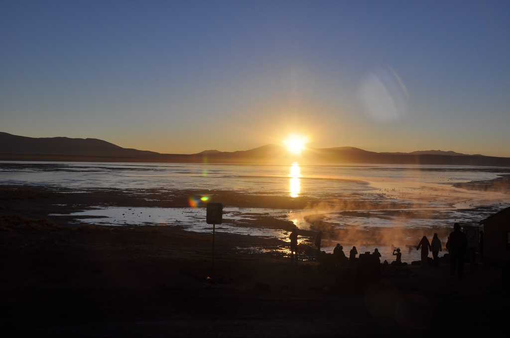 Sunrise dip in a hot spring next to a frozen lake